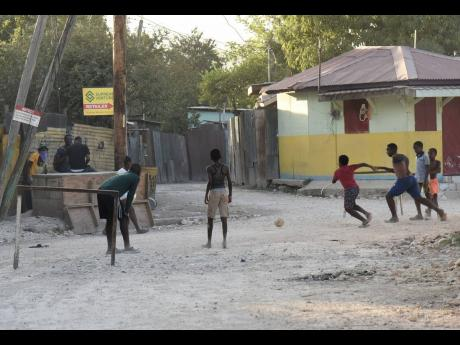 Children enjoying a game of football on one of New Haven's unpaved streets on January 28, 2021.