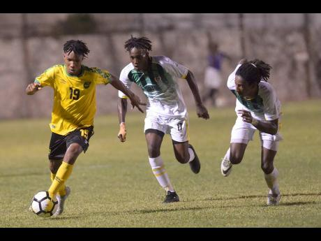 Jamaica's Tyreek Magee (left) dribbles under pressure from Dominican defenders George Usher (centre) and Jolly Fitz during their Concacaf Olympic Qualifier at the Anthony Spaulding Sports Complex in Kingston, Jamaica, on Wednesday, July 17, 2019.