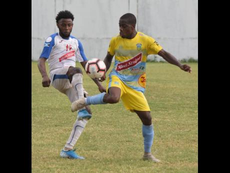Waterhouse's Tremaine Stewart (right) controls the ball ahead of Portmore United's Tevin Shaw during a Red Stripe Premier League match on November 10, 2019.