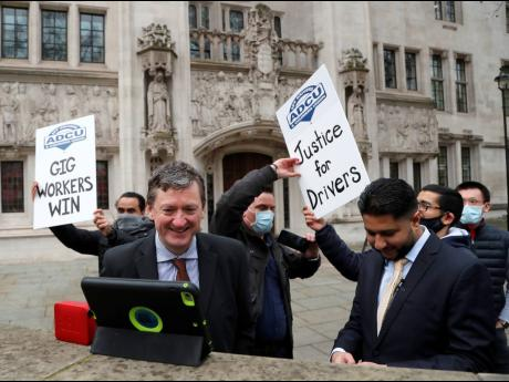 Uber drivers of the ADCU, App Drivers & Couriers Union, celebrate as they listen to the court decision on a tablet computer outside the Supreme Court in London, Friday, February 19, 2021.