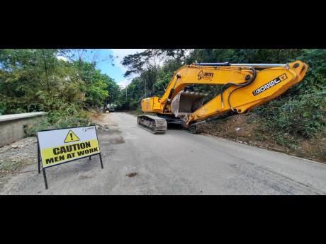 An excavator making its way along the Trinityville main road in St Thomas on Thursday.