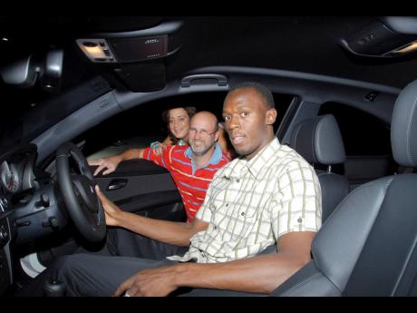 General Manager of Stewart's Automotive Group Duncan Stewart (centre) and Stephanie Scott, creator and conceptualiser of The Gleaner-sponsored Restaurant Week greets track and field star Usain Bolt as he sits inside the new, 2008 BMW M3 Coupe, outside of