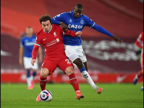 Liverpool's Xherdan Shaqiri (left) vies for the ball with Everton's Abdoulaye Doucoure during the English Premier League match between Liverpool and Everton at Anfield in Liverpool, England, yesterday. Everton won 2-0.