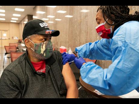 """Reginald Henry, 69, of Washington, receives his second dose of the COVID-19 vaccine at a clinic at Howard University, in Washington. """"I felt confident about getting the vaccine,"""" says Henry, who lives in a senior citzens' building, """"because God hel"""