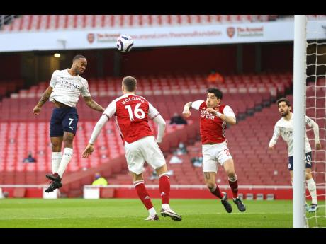 Manchester City's Raheem Sterling (left) scores the goal for his side's 1-0 win over hosts Arsenal in the English Premier League at the Emirates Stadium in London, England, yesterday.