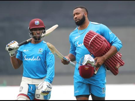 West Indies' white-ball captain Kieron Pollard (right) and Nicholas Pooran walk to bat in the nets during a training session ahead of their first One-Day International cricket match against India in Chennai, India, in December 2019.