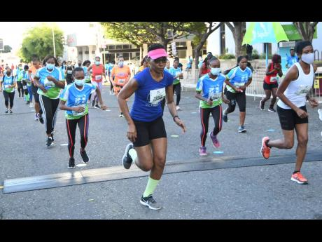 Competitors cross the starting line for the women's 5.5K race at the Sagicor SIGMA Corporate Run held in St Andrew yesterday.