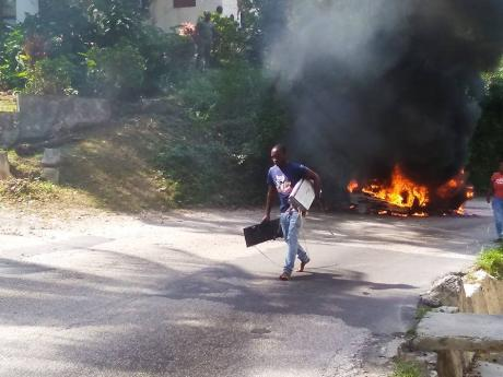 The driver of a Toyota motor car walks away with musical equipment he salvaged from the vehicle, which burst into flames on the Long Hill main road in St James on Sunday.