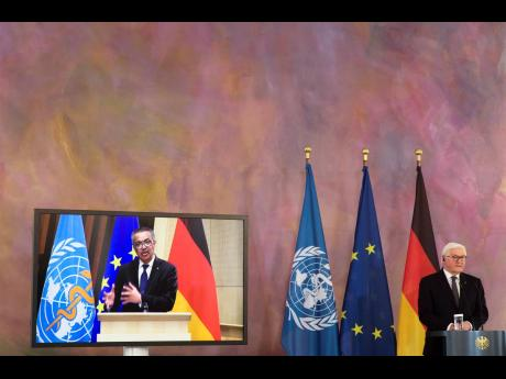 German President Frank-Walter Steinmeier (right) and Director General of the World Health Organization Tedros Adhanom Ghebreyesus (on the screen) brief the media on a virtual joint news conference at Bellevue Palace in Berlin, Germany, yesterday.
