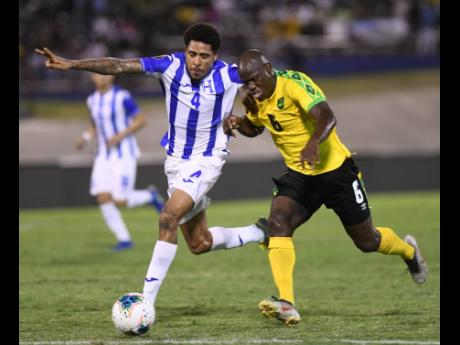 Jamaica's Dever Orgill (right) moves away from Honduran player Henry Figueroa in their Concacaf Gold Cup match held at the National Stadium on June 18, 2019.