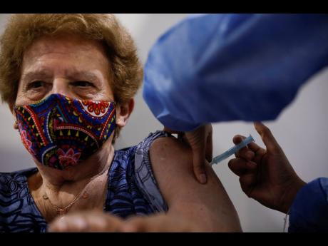 Beatriz de Gregorio gets a shot of the AstraZeneca vaccine for COVID-19 in Buenos Aires, Argentina, on Monday as the capital begins to inoculate people over the age of 80 for the new coronavirus.