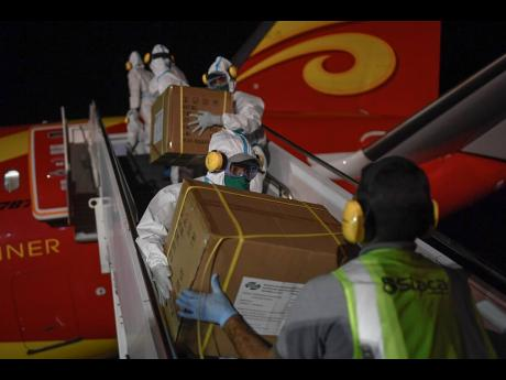 In this March 30, 2020 photo, Venezuelan workers, wearing protective gear as a preventive measure against the spread of the new coronavirus, unload humanitarian aid from China at the Simon Bolivar International Airport in La Guaira, Venezuela.