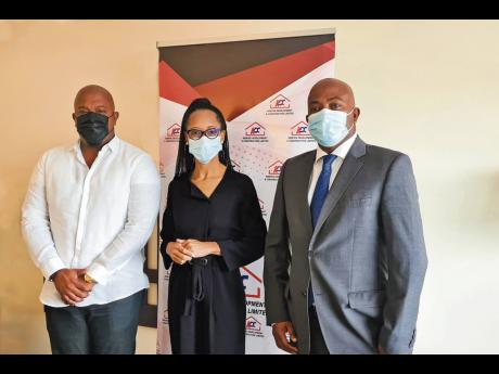 Acting General Manager of the Professional Football Jamaica Limited Arlene Martin (centre) shares lens time with Kemtech Development and Construction executives Karl Tulloch (left) and Garwin Tulloch. Kemtek recently signed on as a club sponsor of the Jama