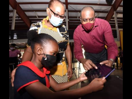 Tasheena Evans (left), grade four student at Allman Town Primary School, pays keen attention to instructions on how to operate a tablet by Courtney Wynter (right), chairman of the Wolmer's board, while Latoya Nesbitt (centre), principal of Allman Town Pr