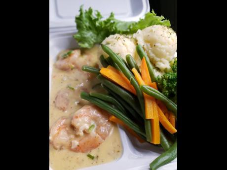 Creamy garlic buttered shrimp with mashed potatoes and steamed and raw vegetables.