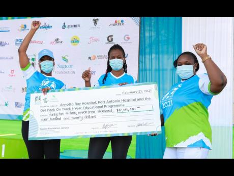 CEOs of the Annotto Bay and Port Antonio hospitals, Marsha Lee (centre) and Althea Gardner (right), pose with their symbolic Sigma Run beneficiary cheques alongside Vice-President of Group Marketing Alysia White. The annual charity event, Sagicor Sigma Run