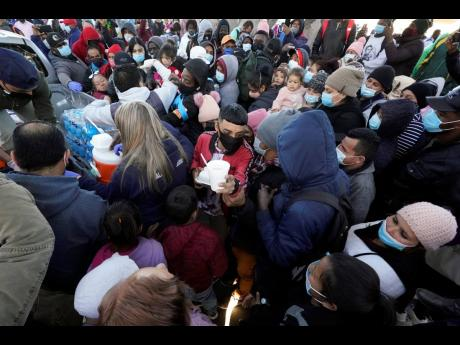 Asylum seekers receive food as they wait for news at the border on February 19 in Tijuana, Mexico.