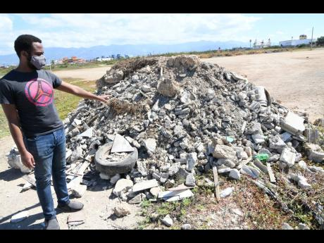 Matthew Williams points to a mound of rubble which contributes to the dust nuisance in the Passagefort area.