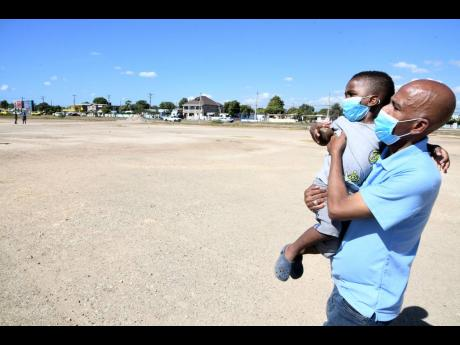 With son Cai-August Williams in hand, Richard Williams, a resident of Passagefort in Portmore, complains about the dust nuisance being caused by a 15-acre piece of land designated to be a climate change park in the municipality.