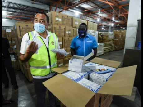 Health and Wellness Minister Dr Christopher Tufton examines syringes for Jamaica's vaccination programme while Dwayne Linton, storage manager at the Shalimar storage facility, looks on. The minister was conducting site visits in Vineyard Town and on Marc