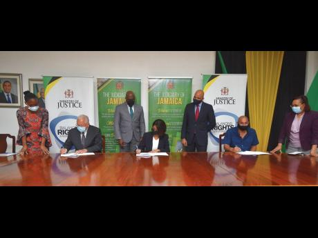 Justice Minister Delroy Chuck (second left) signs a copy of the contract to commence work on the St Ann Family Court. Also signing are Permanent Secretary, Sancia Bennett Templer (centre) and Managing Director of Contraxx Enterprise Limited Stephen Chung.