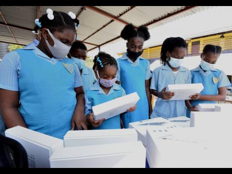 Students of Gregory Park Primary School examine some of the 26 tablets donated to the school by the Kiwanis Club of South St Catherine.