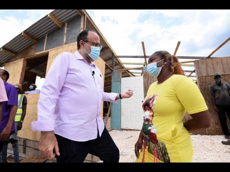 Mark Golding, Opposition leader and president of the People's National Party, listens keenly to Shian Ganpatt, former occupier of lands at Innswood Estate in St Catherine.  Ganpatt was evicted and her home destroyed recently.