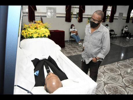 Clyde Jureidini, general manager of Harbour View Football Club, views the body of former national footballer Luton Shelton at the House of Tranquillity Funeral Home on Orange Street in Kingston on Wednesday, February 24, 2021.