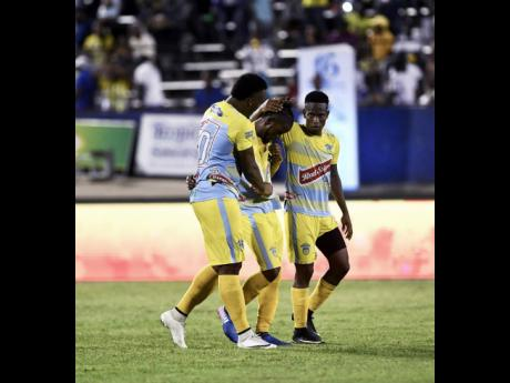 Waterhouse FC players Shawn Lawes (left) and Cardel Benbow (right) console teammate Kemar Beckford after his penalty shootout miss against Portmore United in the Jamaica Premier League final at the National Stadium on April 23, 2018.
