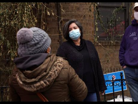 Sofia Moncayo, who leads a food distribution programme through Mosaic West Queens Church in the Sunnyside neighbourhood of the Queens borough of New York speaks with a donation recipient, on Monday. Moncayo and dozens of volunteers distribute more than 1,0