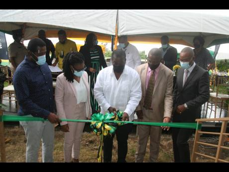 Transport Minister Robert Montague (centre) cuts the ribbon to mark the official opening of a new firehouse and rehabilitated runway at the Negril Aerodrome on Thursday. Looking on are Hanover Western Member of Parliament Tamika Davis (second left) and off