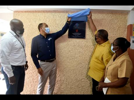 Hardware & Lumber Managing Director Marcus Richards (left) and Nurse Winnifred Reid-Foster (right) look on as Health and Wellness Minister Dr Christopher Tufton (second left) and St Andrew Western Member of Parliament Anthony Hylton unveil a plaque marking