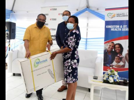 left: Dr Wendy-Ann Byfield Lyons of the Duhaney Park Health Centrer accepts fans from St Andrew Western Member of Parliament Anthony Hylton Health and Welness Minister Dr Christopher Tufton looks on during Thursday's ceremony.