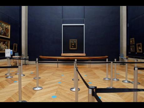 Leonardo da Vinci's 'Mona Lisa' hangs on the wall in a deserted Louvre museum in Paris.