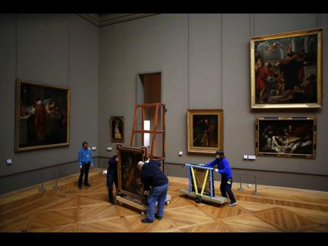 Workers at the Louvre museum handle a painting called Saint Louis, King of France, and his Pageby Spanish painter El Greco, as it returns from an exhibition at the Chicago Institute, in the Louvre museum.