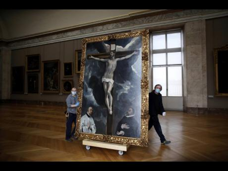 Workers at the Louvre museum transport a painting called 'Christ on the Cross Adored by Two Donors' by Spanish painter El Greco, as it returns from an exhibition at the Chicago Institute, in the Louvre museum, in Paris.