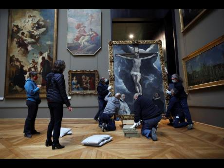Workers handle a painting called 'Christ on the Cross Adored by Two Donors' by Spanish painter El Greco, as it returns from an exhibition at the Chicago Institute, in the Louvre museum, in Paris.
