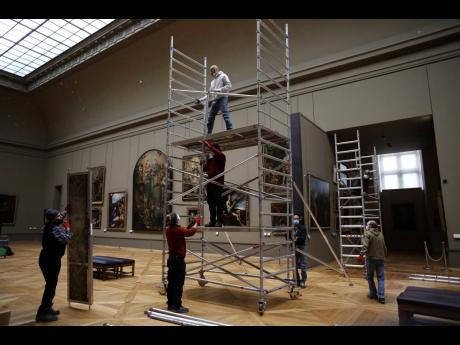 Workers at the Louvre museum set up a scaffolding.