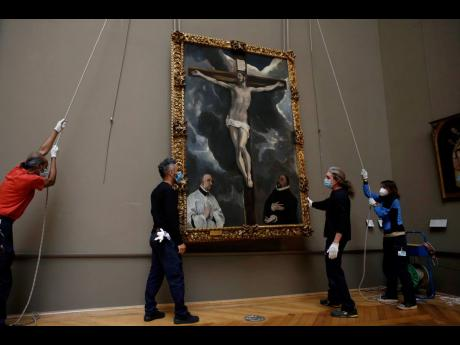 Workers of the Louvre museum lift a painting called 'Christ on the Cross Adored by Two Donors' by Spanish painter El Greco, as it returns from an exhibition at the Chicago Institute, in the Louvre museum in Paris.