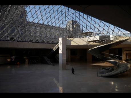 A man walks through the deserted Louvre museum in Paris. It's uncertain when the Louvre will reopen, after being closed on October 30 in line with the French government's virus containment measures. But those lucky enough to get in benefit from a rarif