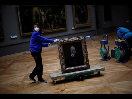 A worker transports the painting called 'Portrait of Antonio de Covarrubias y Leiva' by Spanish painter El Greco, in the Louvre museum.