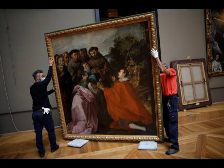 Workers handle the painting called 'The Healing of Saint Bonaventure as a Child by Saint Francis' by Spanish painter Francisco de Herrera, in the Louvre museum in Paris.