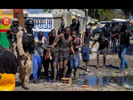 Recaptured inmates are led by police outside the Croix-des-Bouquets Civil Prison after an attempted breakout in Port-au-Prince, Haiti, on Thursday.