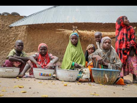 Children play and sell small foodstuffs on the street in the town of Jangebe, where more than 300 girls were abducted by gunmen on Friday from the Government Girls' Junior Secondary School in Zamfara state, northern Nigeria.