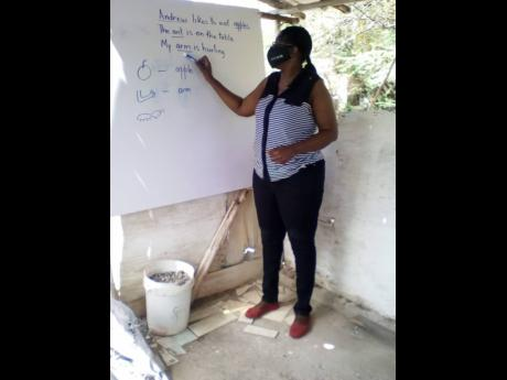 Sharon Allen. a volunteer, teaches students in the Farquhar area. A reading initiatitive has been launched in the community to address the problem of illiteracy.