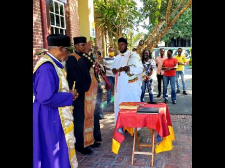 The Head Ethiopian Orthodox Administrator, Komos Archimandrite Abba Gebreyesus Woldesamuel Negatu (centre) conducts prayer services at the Bob Marley Museum on the anniversary of Bob Marley's birth, as other members of the Ethopian community in Jamaica l