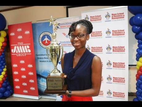 Kristen Gyles with the top prize in this year's Vincent HoSang UWI Venture Competition  for her business model, Factions News, a mobile application that collects news data from citizens across the country for broadcast on various platforms.