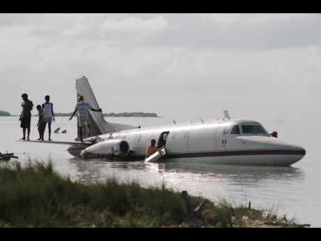 Residents of Rocky Point scavenge for souvenirs from the crash-landed plane.