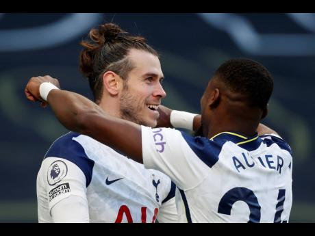 Tottenham's Gareth Bale, (left) celebrates with Serge Aurier during an English Premier League match between Tottenham Hotspur and Burnley at the Tottenham Hotspur Stadium in London, England, yesterday. Spurs won 4-0.