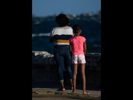 A woman and child look out to sea at the Kingston waterfront on Sunday. A global index has indicated that parents are undergoing increased stress and loneliness.
